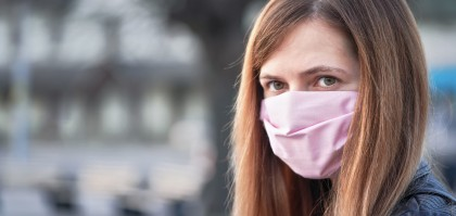 Young woman with hand made face nose mouth mask portrait, blurred empty city square behind her. Can be used during coronavirus covid-19 outbreak prevention